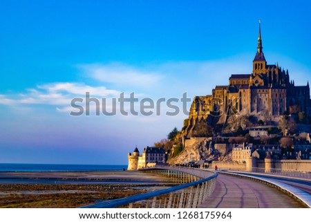 Medieval castle, against the blue sky and white clouds, the castle on the island, the castle is surrounded by water, green grass, a fortress and abbey, an incredibly beautiful castle like  fairy tale #1268175964