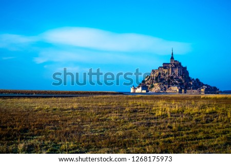 Medieval castle, against the blue sky and white clouds, the castle on the island, the castle is surrounded by water, green grass, a fortress and abbey, an incredibly beautiful castle like  fairy tale #1268175973