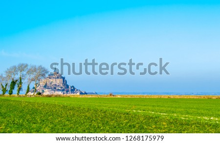Medieval castle, against the blue sky and white clouds, the castle on the island, the castle is surrounded by water, green grass, a fortress and abbey, an incredibly beautiful castle like  fairy tale #1268175979