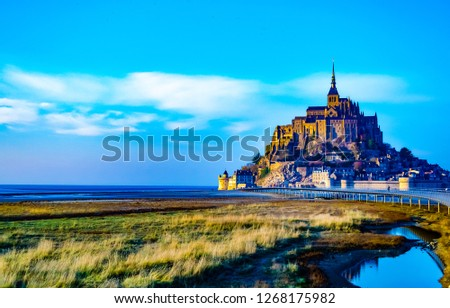 Medieval castle, against the blue sky and white clouds, the castle on the island, the castle is surrounded by water, green grass, a fortress and abbey, an incredibly beautiful castle like  fairy tale #1268175982