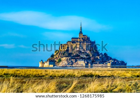Medieval castle, against the blue sky and white clouds, the castle on the island, the castle is surrounded by water, green grass, a fortress and abbey, an incredibly beautiful castle like  fairy tale #1268175985