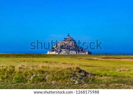 Medieval castle, against the blue sky and white clouds, the castle on the island, the castle is surrounded by water, green grass, a fortress and abbey, an incredibly beautiful castle like  fairy tale #1268175988