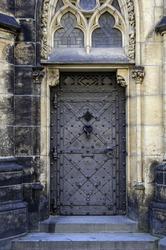 Medieval castle door with door knocker, handle and ornaments.