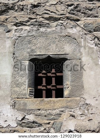 medieval castle near Aosta - details of a window with iron grating
