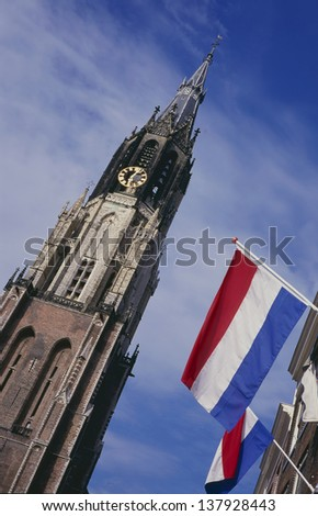 Medieval church tower of the so called New Church and flags at the market place in Delft, the Netherlands. In this church the Dutch Royal family is buried.