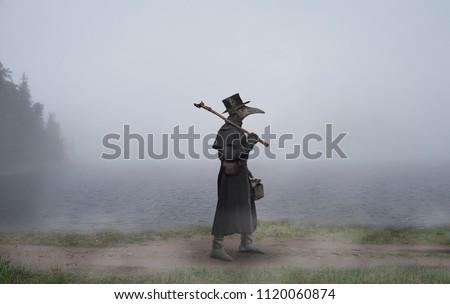 Medieval era. The plague doctor walks along the road near the misty lake Stockfoto ©