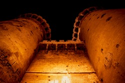 Medieval fort towers 'Torres de Quart' with visable canon shots in orange illuminated night in Valencia, Spain