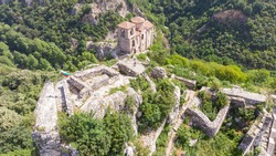 Medieval Fortress Asen , on a hill in eastern Europe, Bulgaria. Bulgarian antique and heritage stronghold fortification on a rock. Aerial view of a holy place and monastery. Tourist place with forest.