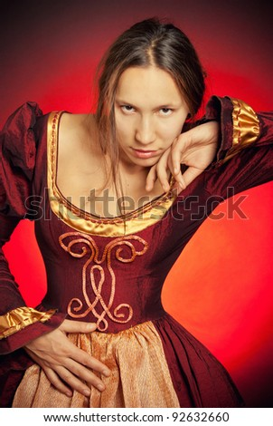 Medieval girl in the maroon dress with disheveled hair