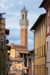 Medieval gothic bell tower  Torre del Mangia of Palazzo Pubblico (town hall) seen from the narrow streets of Siena, Italy old town on a sunny day with blue sky