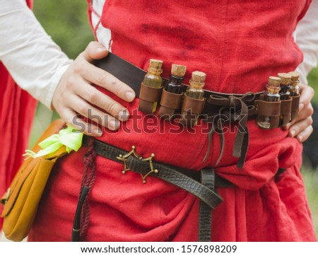 medieval healer leather belt with small jars worn over a red dress