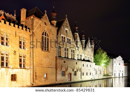 Medieval houses on canal in Bruges at night, Belgium - stock photo