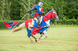 Medieval knight costume on a horse and man with flag