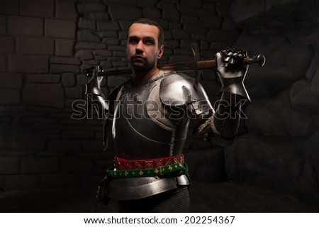 Medieval Knight posing with sword in a dark stone background. Waist up portrait.