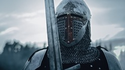 Medieval Knight Wearing Armour and Helmet, Draws Sword from Shearh, Ready to Fight, Kill His Enemy in Battle. Warrior Soldier on Battlefield. War, Invasion, Crusade. Cinematic Historic Reenactment