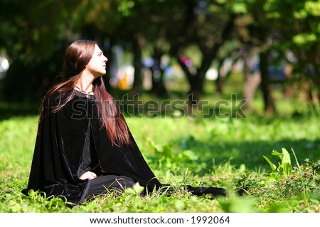 Medieval lady with black mantle on the grass for Halloween carnival