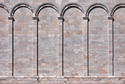 Medieval marble stone wall with arcs. Classical wall with columns and arches. Architectural decoration background.