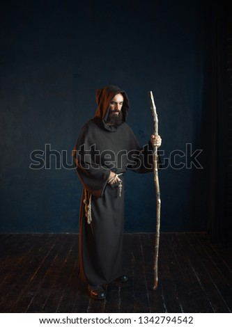 Medieval monk in robe with hood rests on a stick Сток-фото ©