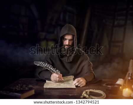 Medieval monk in robe writes with a goose feather #1342794521