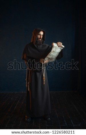 Medieval monk reads a prayer in ancient manuscript Сток-фото ©