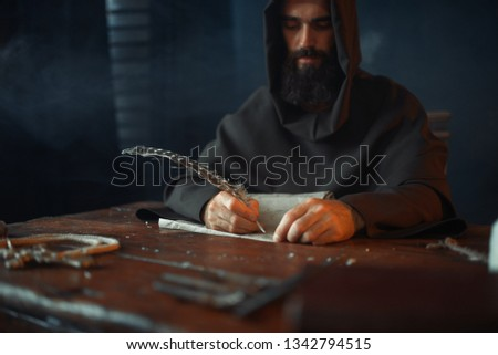 Medieval monk sitting at table and write, top view Foto stock ©