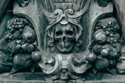 Medieval ornament with symbols of death and skull on a tombstone in a cemetery.