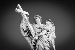 Medieval outdoor statue of an Angel with the Cross on Sant'Angelo Bridge in black and white with vignetting effect in Rome, Lazio region, Italy