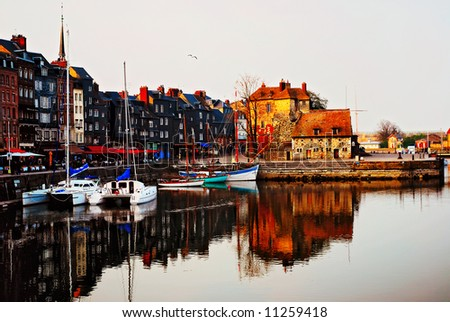 Medieval part of Honfleur harbor in Calvados, France at the late sunset with yachts, restaurants and shops.