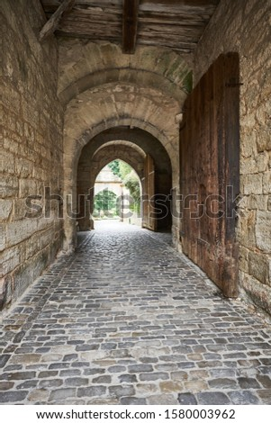 Medieval passageway under the village ramparts with old wooden gate, cobblestone path leading out into the gardens and parkland in the distance.                               #1580003962