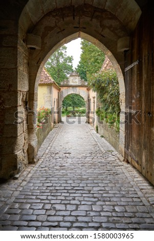 Medieval passageway under the village ramparts with old wooden gate, cobblestone path leading out into the gardens and parkland in the distance.                               #1580003965