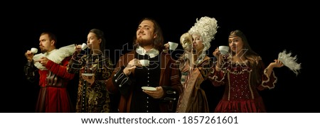Medieval people as a royalty persons in vintage clothing drinking coffee, tea on dark background. Concept of comparison of eras, modernity and renaissance, baroque style. Creative collage.