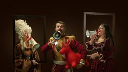 Medieval people as a royalty persons in vintage clothing shouting with loudspeaker on dark background. Concept of comparison of eras, modernity and renaissance, baroque style. Creative collage.
