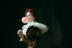 Medieval redhead young woman in golden vintage clothing as a duchess with red sunglasses blowing a bubblegum on dark green background. Concept of comparison of eras, modernity and renaissance.