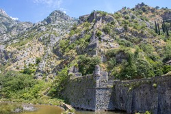 Medieval security wall surrounding the old town. Military tower. Ruins of a fortress at the top of the mountain. Fortifications of Kotor, Montenegro.