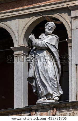 Medieval statue of Saint Peter the Martyr with a hatchet in his head decorating the facade of the Cremona Cathedral. #435751705