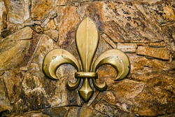 Medieval stone wall with fleur de lis symbol engraved on the wall