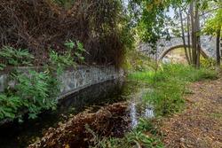 Medieval stoned bridge water flowing in the river in autumn. Kalopanayiotis village Troodos mountains Cyprus