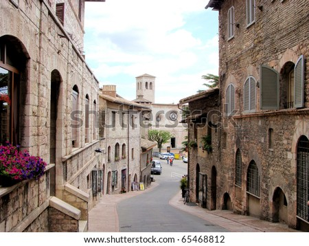 Medieval street in Assisi, Italy and the church San Pietro behind