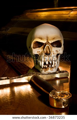 Medieval sword and spooky skull lit by candles - stock photo