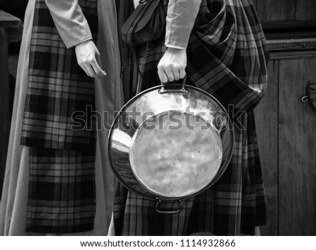 Medieval talk. Two women chatting at Medieval festival. One of them holding shiny pan and the other small piece of bread. France. Black and white photo.