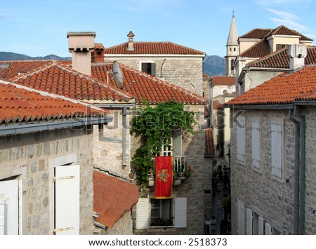 Medieval town Budva in Montenegro, view from town wall, with montenegro flag - stock photo