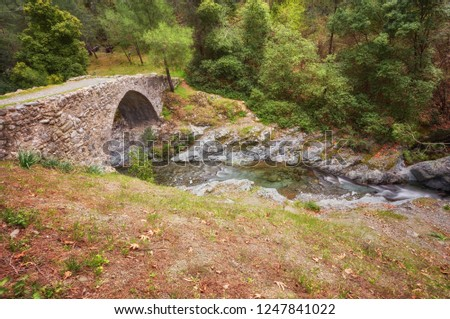 Medieval Venetian bridge in the canyon among rocks at sunny spring evening. Cyprus bridge Elia.