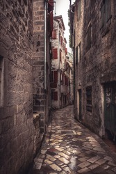 Medieval vintage narrow street with ancient stone pavers with medieval buildings in old european city Kotor in Montenegro