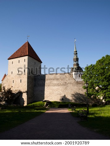 Medieval walls with a tower and a spire - a fragment of the satra city of Tallinn, in summer. Stok fotoğraf ©