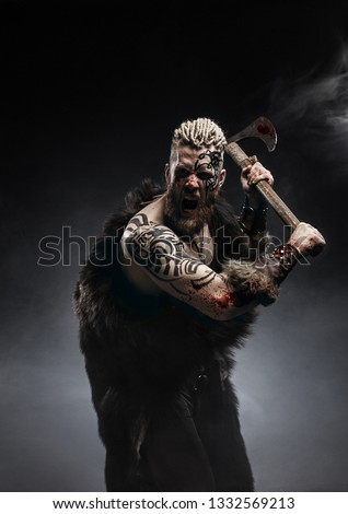 Medieval warrior berserk Viking with tattoo and in skin with axe attacks enemy