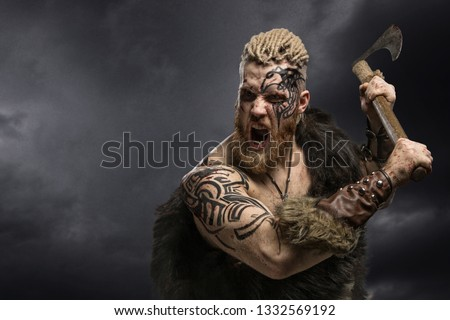 Medieval warrior berserk Viking with tattoo and in skin with axe attacks enemy. Close-up portrait