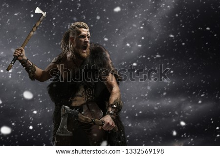 Medieval warrior berserk Viking with tattoo and in skin with axes attacks enemy. Concept photo
