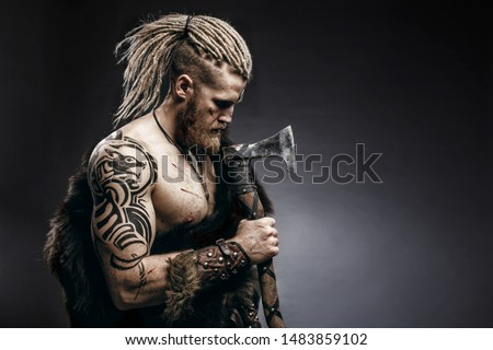 Medieval warrior berserk Viking with tattoo on skin, red beard and braids in hair with axe and shield attacks enemy. Concept historical photo ストックフォト ©