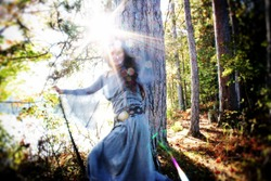 Medieval woman in whirling motion by a misty early morning lake. Green Witch or Shamanic story. She is holding a staff within lens flare and evokes powerful energy.