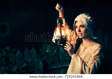 Medieval Woman with Vintage Lantern Outside at Night - Cosplay girl in Halloween costume holding a lamp